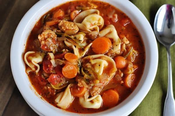 top view of a sausage tortellini and veggie soup in a white bowl