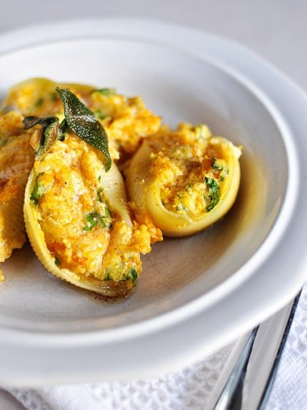 a white plate with stuffed butternut squash and sage pasta shells