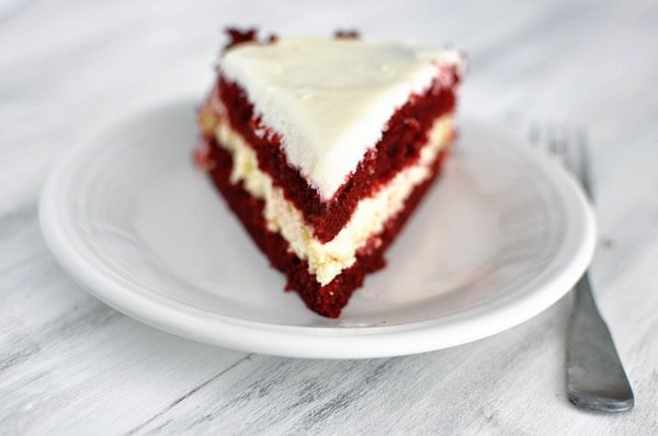 a piece of layered red velvet cheesecake cake on a white plate
