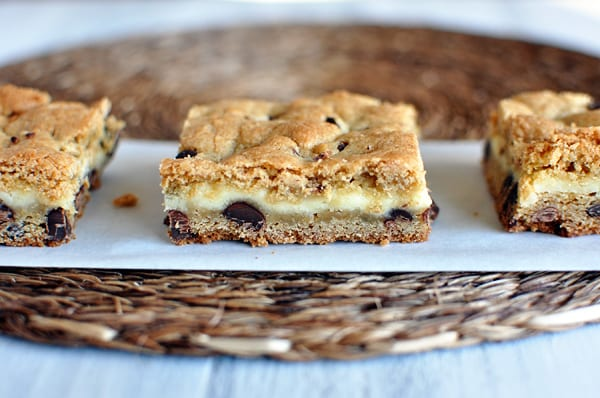 three chocolate chip bars with a cheesecake middle lined up on a sheet of parchment paper