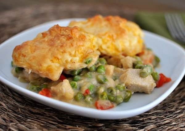 a white plate with a chicken and vegetable filling topped with a cheddar biscuit topping
