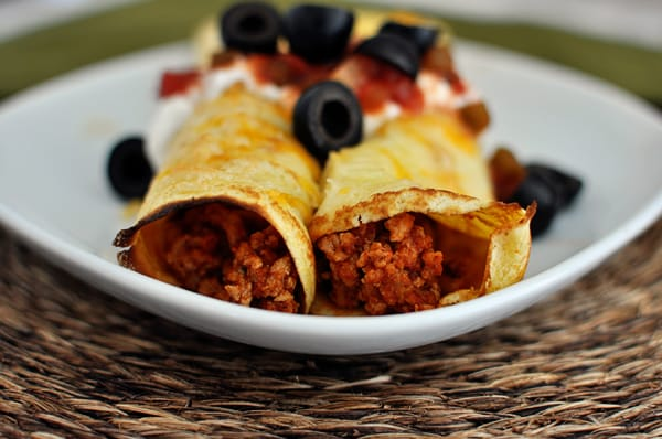 white plate with two cornmeal enchilada filled crepes topped with black olives, salsa, and sour cream
