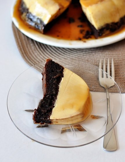 a piece of chocolate flan cake on a glass plate with the rest of the cake in the background