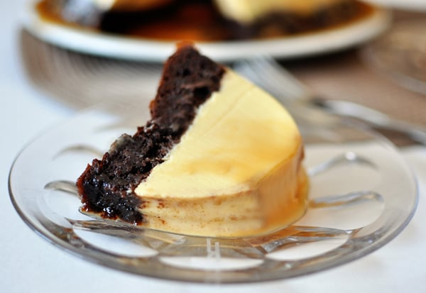 a piece of chocolate flan cake on a glass plate