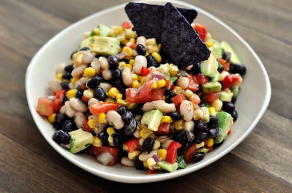 a white bowl full of bean, corn, and avocado dip