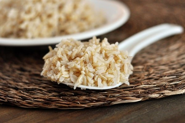 a spoonful of cooked brown rice with a plate of rice in the background