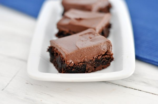 top view of three chocolate frosted brownies on a white rectangular platter