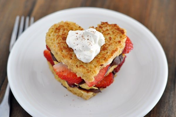 top view of a heart shaped chocolate and strawberry stuffed french toast on a white plate