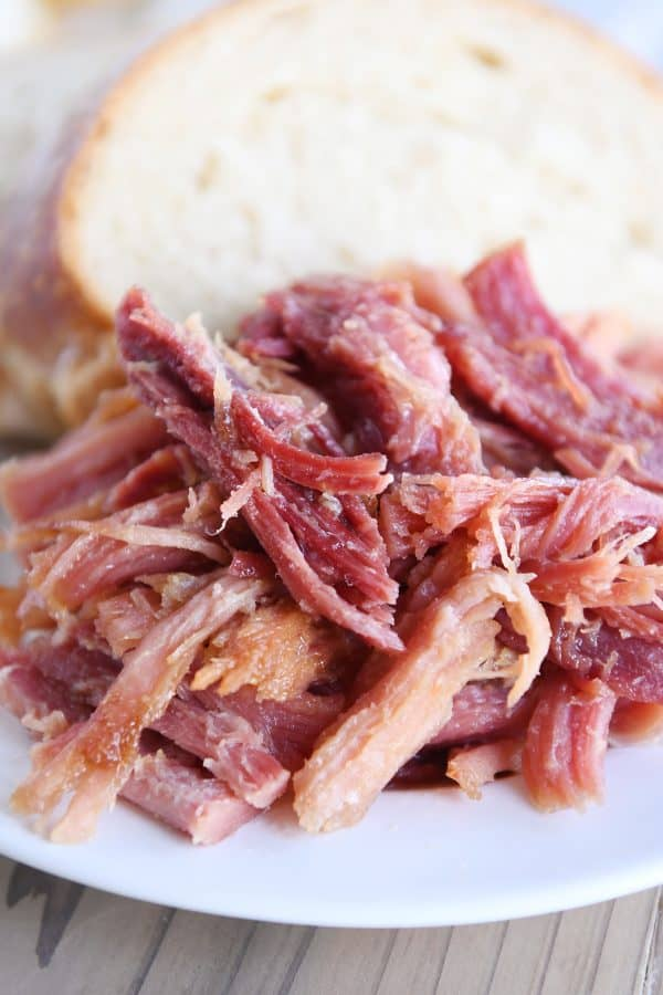 close up of sweet baked ham on white plate with bread
