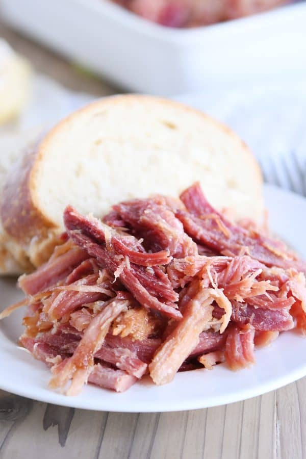 pile of sweet baked ham on white plate with bread
