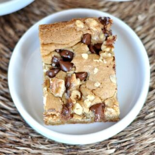 top view of a walnut chocolate chip blondie square on a white plate