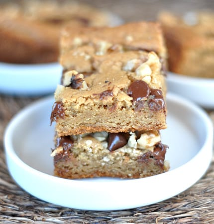 two walnut and chocolate chip blondies stacked on a white plate