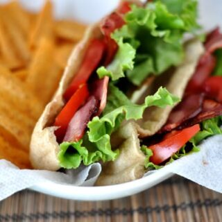 a cut open BLT pita pocket next to some chips in a white paper-lined basket
