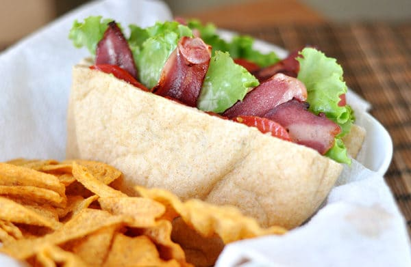a cut open BLT pita pocket and chips in a paper lined basket
