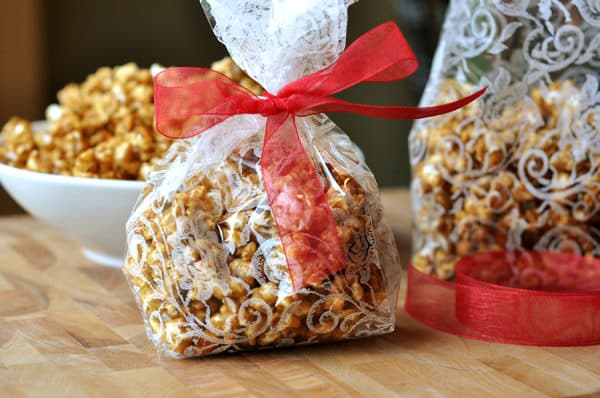 decorative plastic bags filled with toffee popcorn and tied with a red ribbon