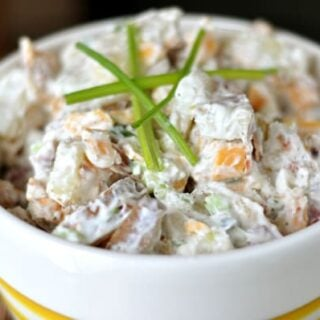 white bowl full of baked potato salad with sprigs of chives on top