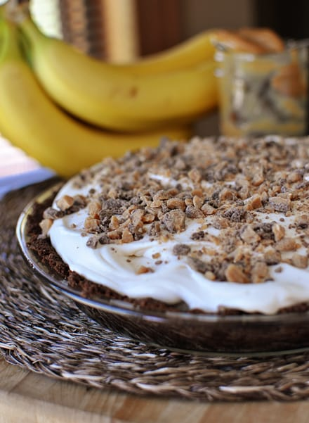 a chocolate crust banana pie with whipped cream and chopped toffee bits in a glass pie dish and bananas in the background