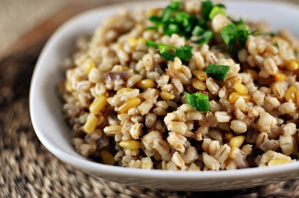 white bowl with cooked barley and pine nuts, and topped with green onions
