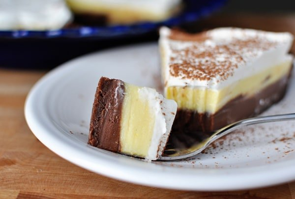 a slice of black bottom pudding pie with whipped topping and a bite taken out on a white plate
