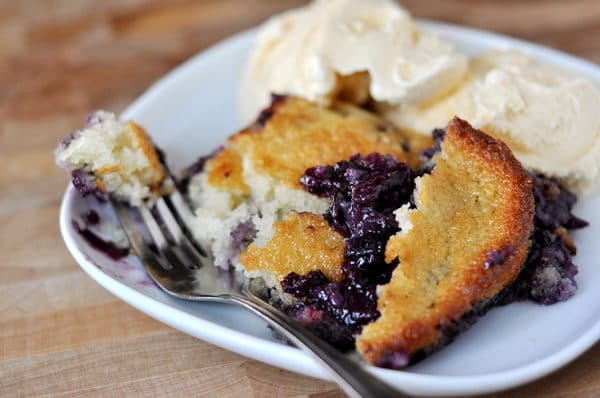 square white plate with fresh blueberry cobbler and vanilla ice cream on the side