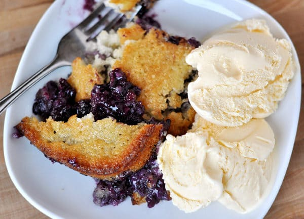 top view of a white plate with baked blueberry cobbler and vanilla ice cream on the side