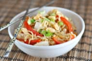 white bowl with noodles, sliced red peppers, chicken, and edamame