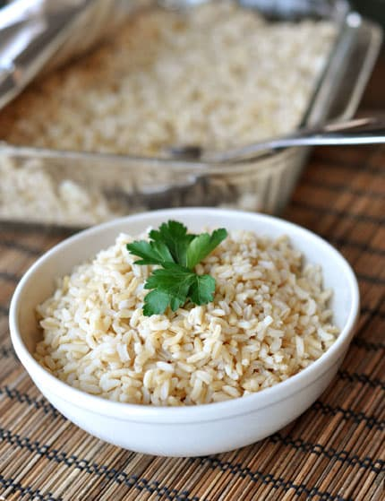 white bowl with baked brown rice and topped with parsley