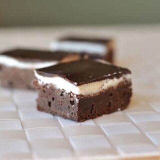 three fudgy brownies with a middle layer of white frosting and topped with chocolate ganache