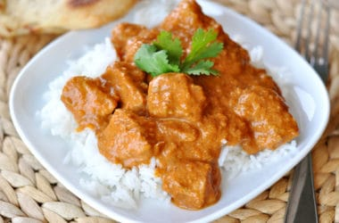 white dish with white rice and chicken with indian butter sauce on top