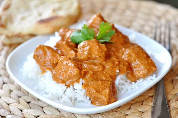 a white dish with rice and indian chicken and sauce on top