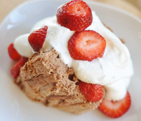 large slice of angel food cake topped with whipped cream and sliced strawberries
