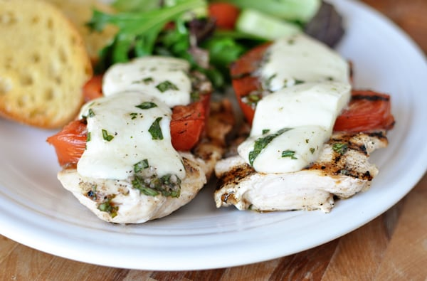 grilled caprese chicken breasts in front of a salad and garlic bread on a white plate