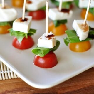 white platter with halved cherry tomatoes, a basil leaf, and a cube of fresh mozzarella skewered on toothpicks