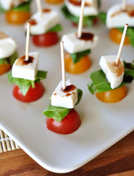 white platter with toothpick caprese skewers