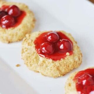 cheesecake cookies with a cherry center lined up on a white plate