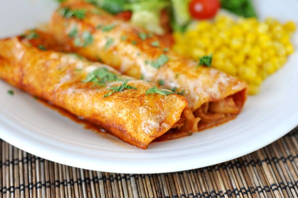 Two red sauce enchiladas on a white plate, with corn and a green salad on the side.