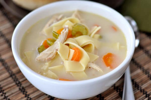top down view of a white bowl full of chicken noodle soup with sliced carrots and celery