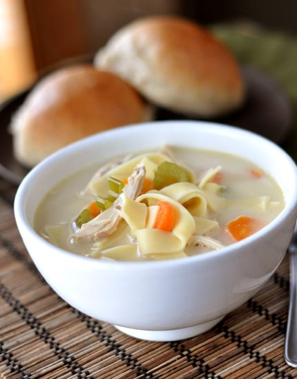 a white bowl full of chicken noodle soup with rolls in the background