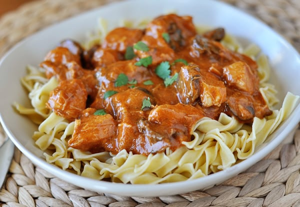 white bowl of cooked noodles with cubes of chicken and an orange paprika sauce