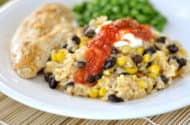 white plate with a large serving of rice with black beans and corn and topped with salsa, next to a chicken breast and green peas