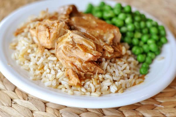 a white plate with brown rice, shredded pork on top of the rice, and green peas next to the rice