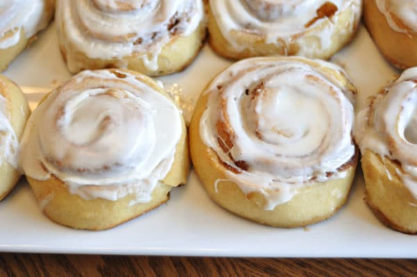 top view of small frosted cinnamon rolls on a white platter