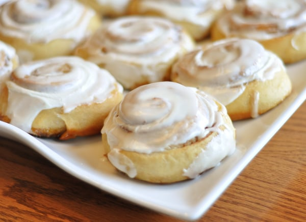white platter with small frosted cinnamon rolls