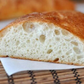 a loaf of ciabatta bread sliced open on a white napkin