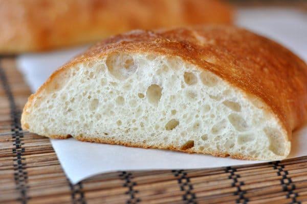 a loaf of ciabatta bread sliced open on a white napkin