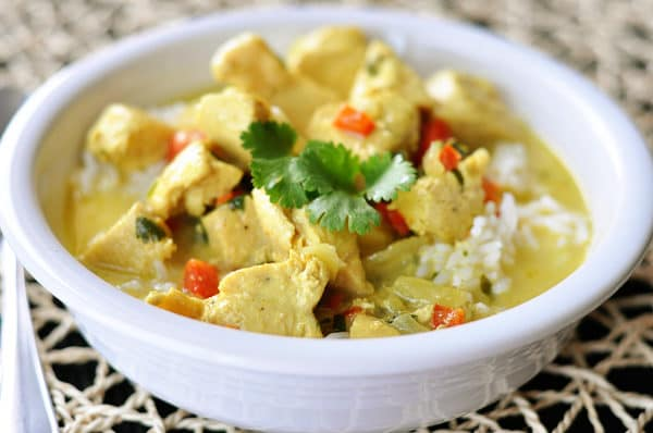 a white bowl of chicken curry soup over white rice