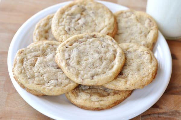 a top down view of a white plate full of toffee studded cookies