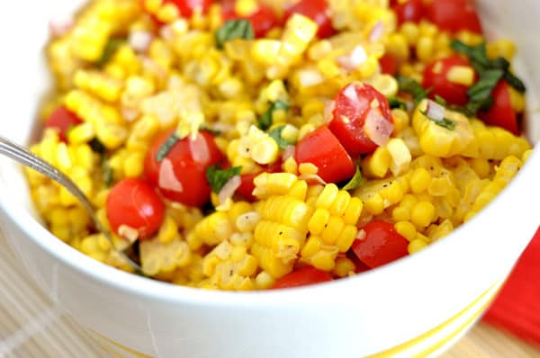 white bowl with a corn, tomato, and basil salad