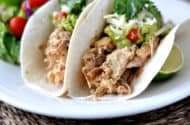 soft shell tacos filled with pork and toppings all on a white plate