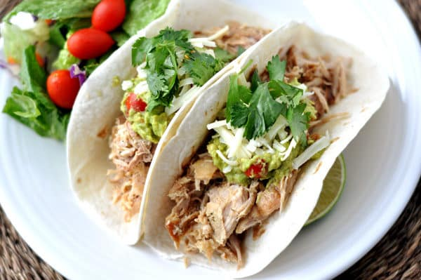 top view of two soft shell tacos filled with pork and toppings all on a white plate